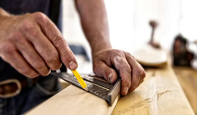 carpenter measures on piece of wood marks with pencil