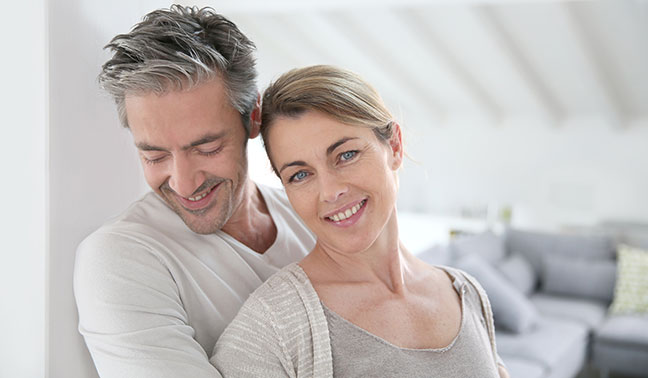 man with arms around woman smiling