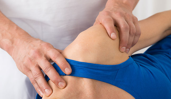physiotherapist does manual therapy on shoulder