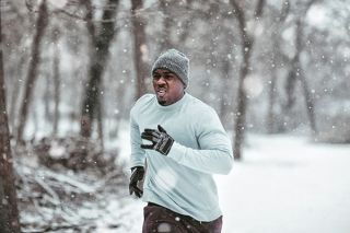 Man running in the winter in the woods