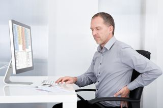 Man sitting at a computer with back pain