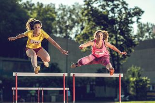 two women running hurdles
