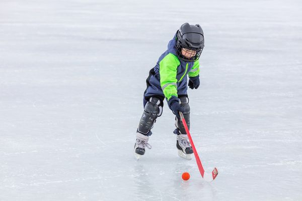 a child playing hockey outdoors alone