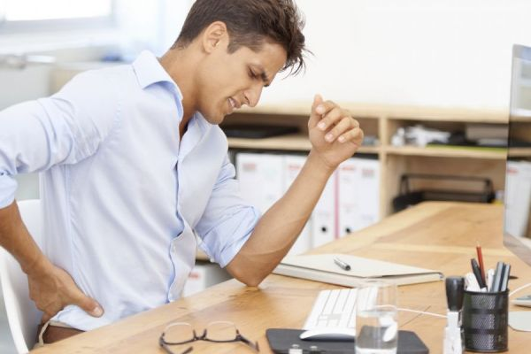 Male at desk with back pain