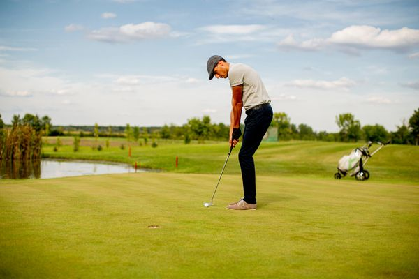 A man out in the golf course in the summer