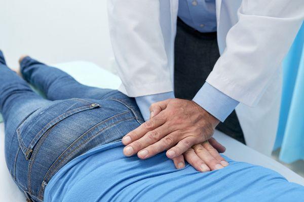 Chiropractor doing pushing motion to adjust back