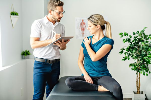 A clinician talking to a woman about her shoulder problem