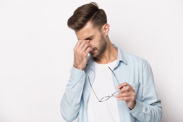 a man taking off his glasses, rubbing his eyes due to dizziness.
