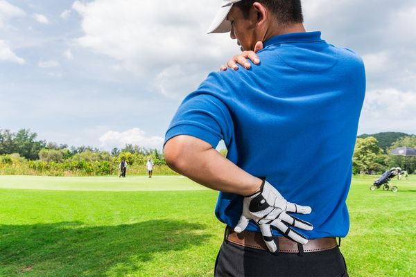 a man experiencing back pain due to golf