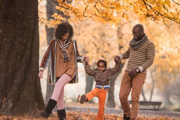 couple with a child moving among fall leaves