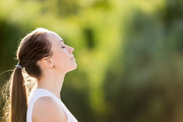 Calm young woman with a ponytail with eyes closed, enjoying fresh air outdoors