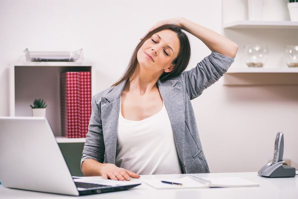 a woman in front of a desk doing neck exercises