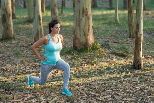 a woman doing pelvic stretches outside
