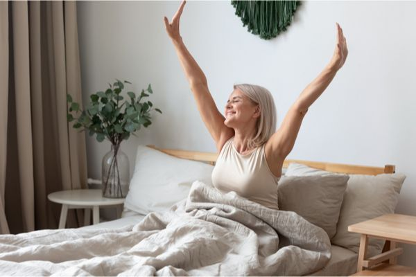 an elderly woman waking up, feeling refreshed