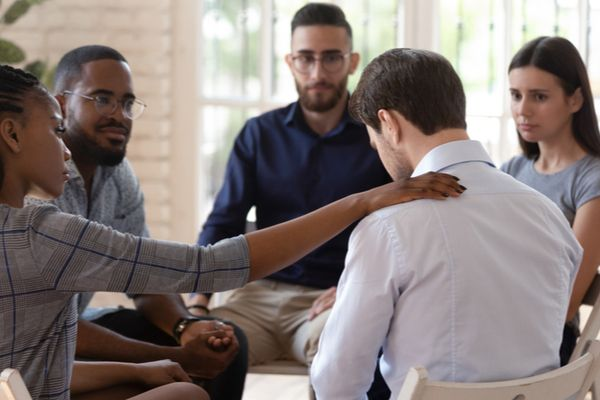 a man being comforted in a group therapy session