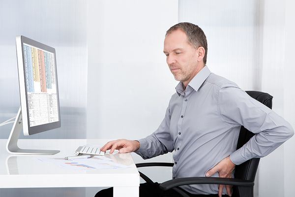 man sitting at a desk with sore back