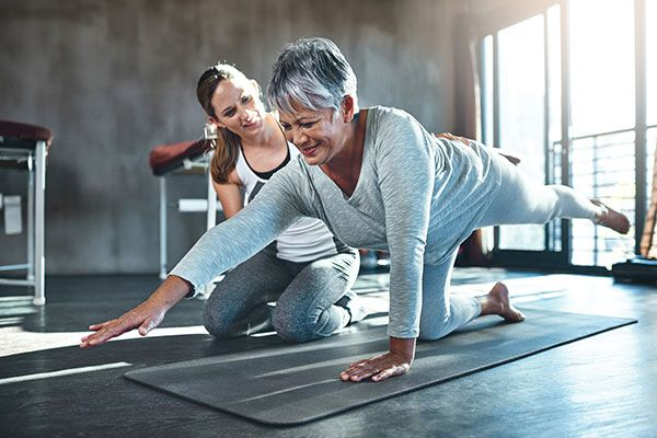 physiotherapist with a patient on a yoga mat exercising with cancer