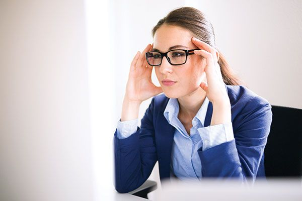 Woman with glasses at the computer and with a headache