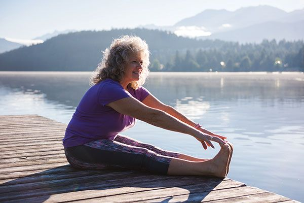 woman stretching her legs on a dock in front of water
