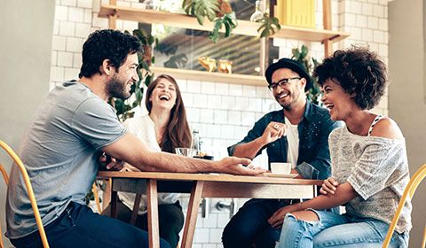 four friends at a cafe laughing