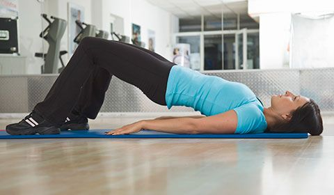 woman doing hip lift exercise on a mat