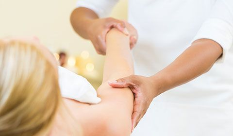 physiotherapist massage upper arm of patient