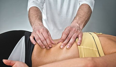physiotherapist pinches back of patient