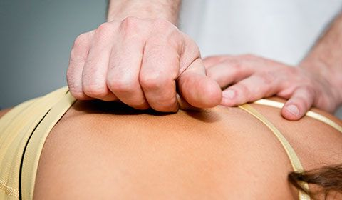 therapist using myofascial release techniques on patients back