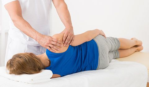 physiotherapist manipulates shoulder of patient