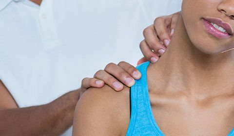 performing physiotherapy on a woman's shoulder