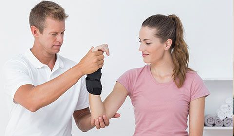 physiotherapist holds arm of patient with wrist brace