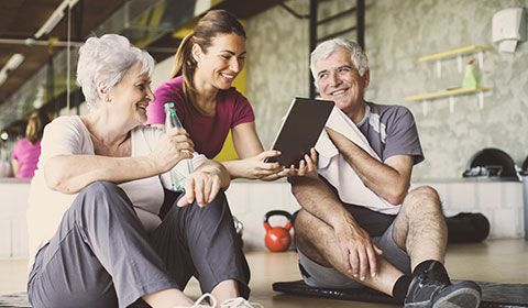 physiotherapist sits with senior couple in the gym