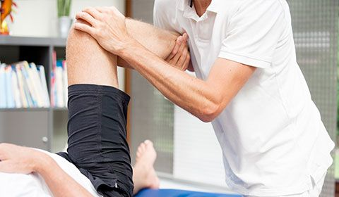 Physiotherapist working on patients leg