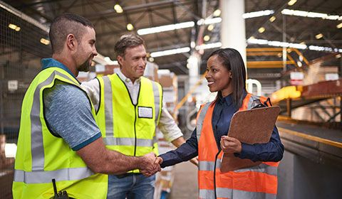 three people in warehouse talking shaking hands