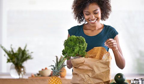 woman kitchen unpacking grocery bag broccoli pineapple