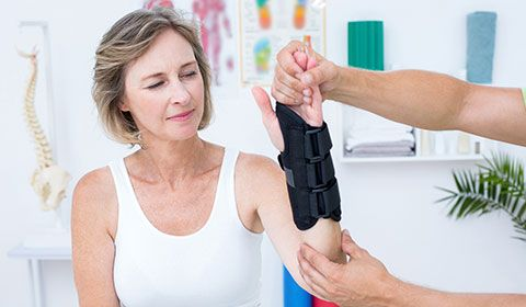 woman at physiotherapist with wrist brace