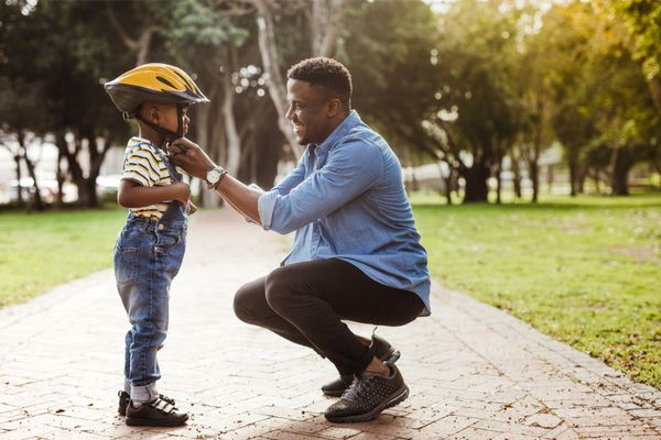 A man helping a child put on a helmet outside