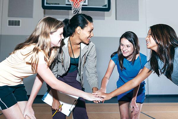 women huddled around their basketball coach