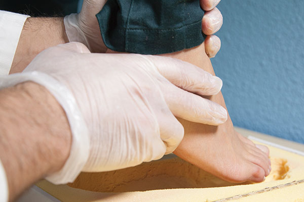 Doctor fitting man with orthotic