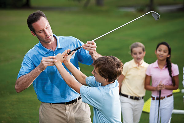instructor teaching kids how to golf