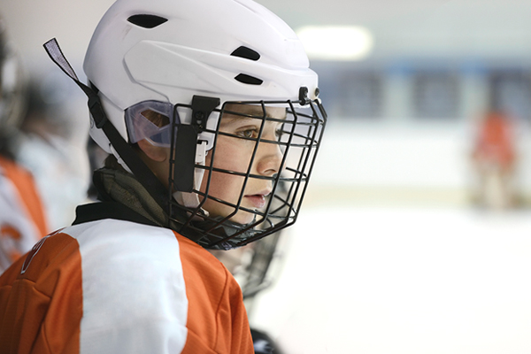 kid playing hockey and sitting on the bench