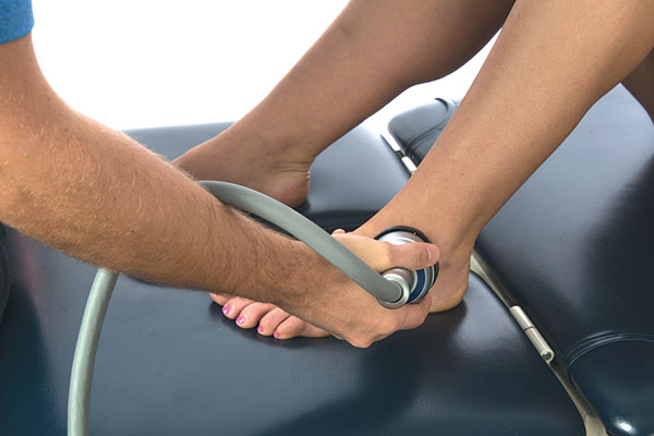 man receiving shockwave therapy to leg