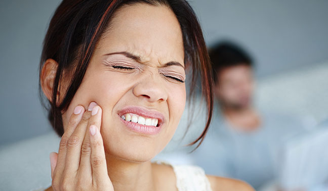 Women holding a sore jaw